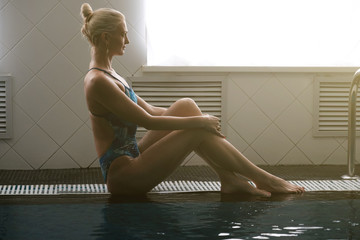Beautiful young woman sitting on the edge of the pool in profile in the sun.