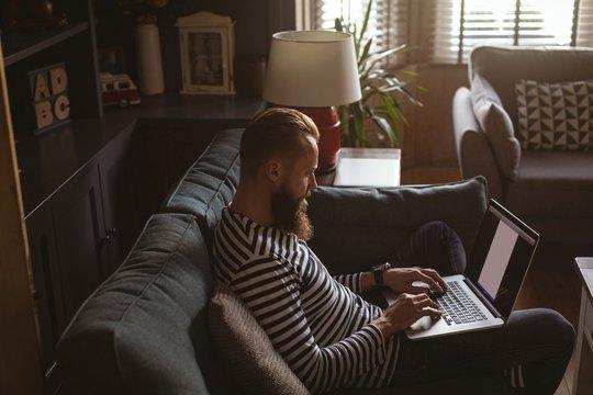 Man sitting on sofa using his laptop
