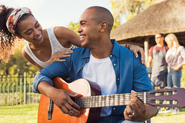 Happy man playing guitar outdoor