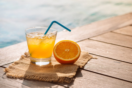 Close up of screwdriver cocktail alcohol drink with orange juice, slices and ice standing near the pool. Refreshing iced lemonade beverage in glass by the poolside. Sun glares. Background, copy space.