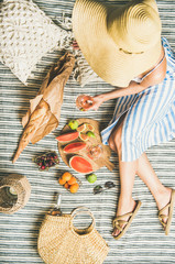Aluminium Prints Picnic Summer picnic setting. Woman in linen striped dress and straw sunhat with glass of rose wine in hand, fresh fruit and baguette on blanket, top view. Outdoor gathering or lunch