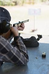 Man aiming shotgun at target in shooting range