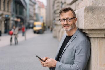 mann mit anzug steht in der innenstadt und hält sein mobiltelefon in der hand