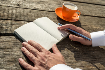 Closeup of the hands of a man ready to write in front of an open notebook with blank pages
