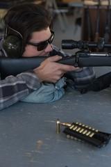 Man aiming sniper rifle at target in shooting range