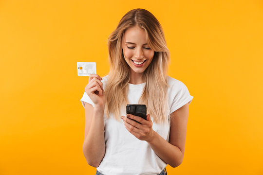 Portrait of a happy young blonde girl showing plastic credit