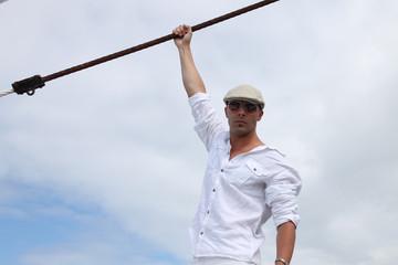 retrato hombre atractivo el aire libre vestido de blanco con gafas de sol y sombrero sujetandose a una cuerda