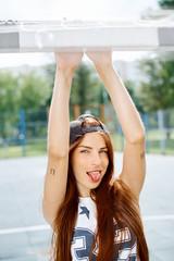 Beautiful young girl in a cap showing tongue