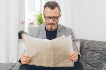 mann sitzt auf dem sofa und liest die tageszeitung