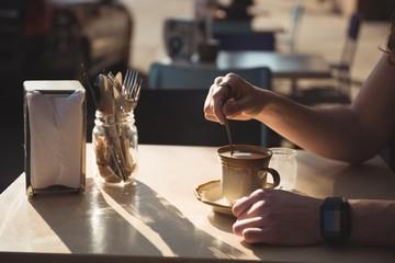 Man stirring coffee with spoon