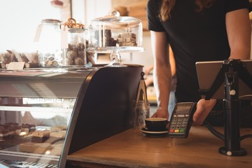 Mid section of waiter receiving payment at counter