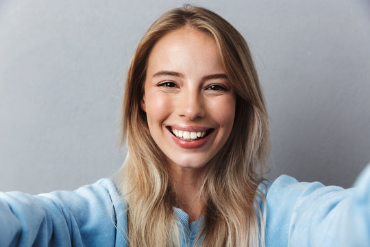 Close up of smiling young blonde girl taking a selfie
