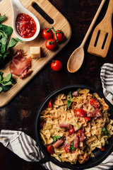 elevated view of pasta with jamon, pine nuts, sauce, cherry tomatoes, mint leaves covered by grated parmesan in pan surrounded by kitchen towel and cutting board with ingredients on table