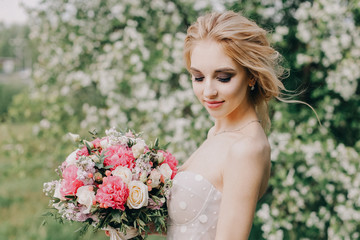 beautiful bride in a wedding dress with a bouquet in her hands on the background of blooming Apple trees