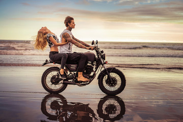 side view of young couple riding motorcycle on ocean beach