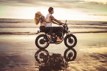 side view of girlfriend hugging boyfriend from back on motorcycle on ocean beach