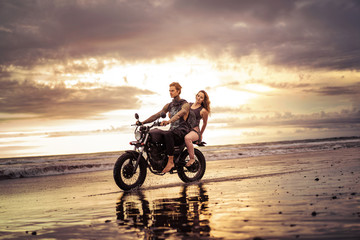 couple riding motorcycle on ocean beach with beautiful sunrise on background
