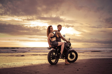 boyfriend and girlfriend sitting on motorcycle at beach during sunrise and looking at camera