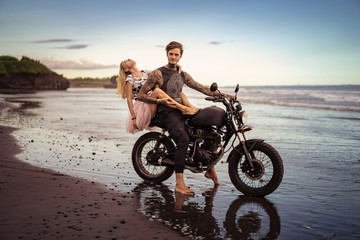 passionate couple hugging on motorbike on ocean beach during beautiful sunrise