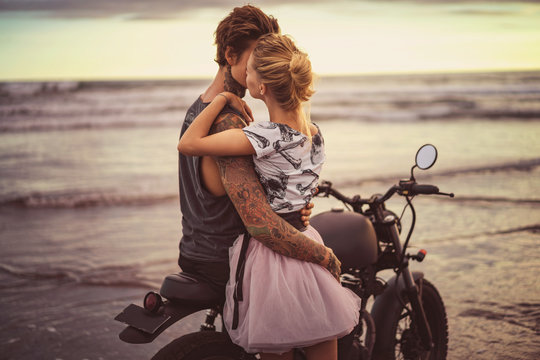 passionate couple hugging on motorcycle on ocean beach during beautiful sunrise