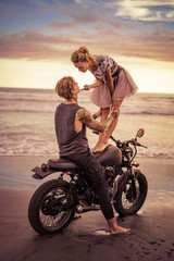 girlfriend standing on motorcycle and touching boyfriend chin on ocean beach