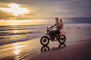 boyfriend and girlfriend sitting on motorcycle on ocean beach during sunrise