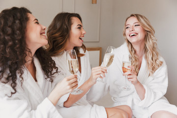 Photo of joyful three women 20s wearing housecoat smiling and lying in big bed in luxury apartment or hotel room with glasses of champagne, during hen party