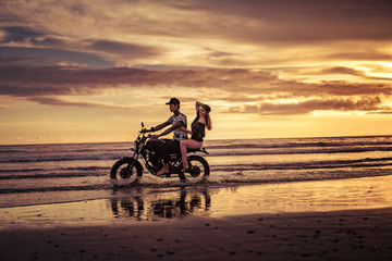affectionate couple riding motorcycle on ocean beach