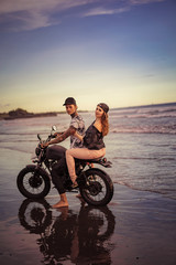side view of couple riding motorcycle on seashore