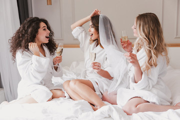 Portrait of pretty three women 20s celebrating bachelorette party and drinking glasses of champagne in luxuty apartment or hotel room, while bride trying on wedding veil