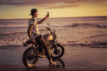tattooed man sitting on motorbike at seashore and taking photo of sunrise with smartphone