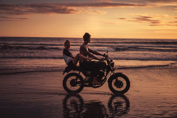 side view of couple having fun and riding motorcycle on ocean beach