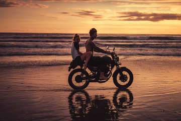 couple riding motorcycle on ocean beach