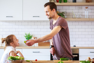 Picture of father with small daughter cooking vegetables