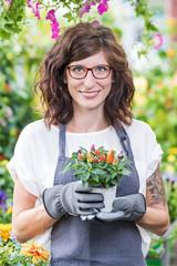 Gärtnerin im Gewächshaus hält lächelnd einen Topf mit Zierpaprika in den Händen