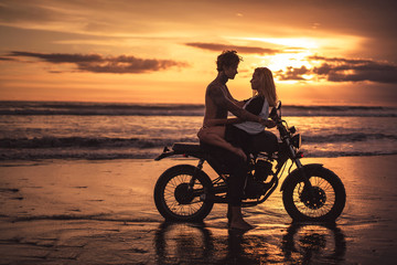 passionate boyfriend and girlfriend cuddling on motorbike at beach during sunset