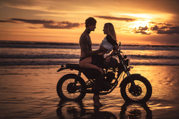sensual couple hugging on motorbike at beach during sunset