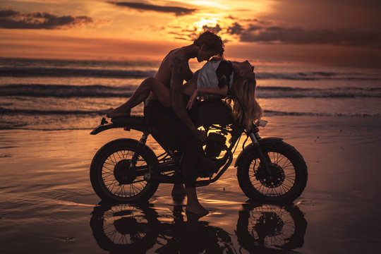 sexy couple hugging on motorbike at beach during sunset