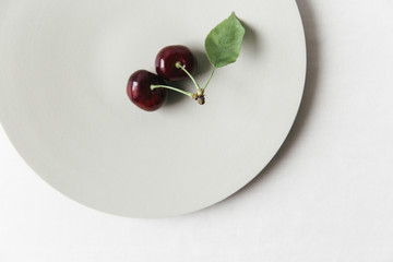 Cherries on a plate on a white surface.