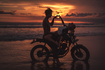 passionate couple making heart with fingers on motorcycle at beach during sunset