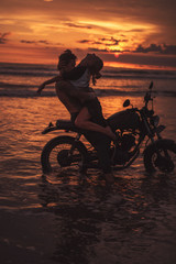 sexy boyfriend and girlfriend hugging on motorcycle at beach during sunset