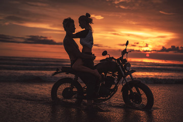 seductive couple hugging on motorcycle at beach during sunset