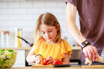 Picture of man with daughter cooking vegetables