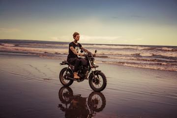 handsome tattooed biker riding motorbike on ocean beach during vacation