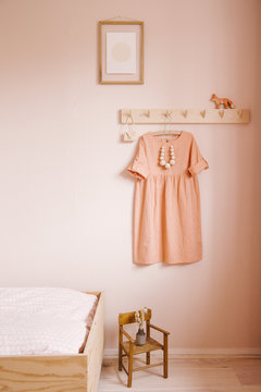 A girls bedroom scene with a coatrack, dress, bed, chair and tiny art work.