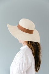 Woman seen from the back wearing a straw sun hat.