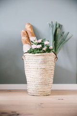 A rush or wicker basket with light pink roses, with two baguettes and a couple of leeks.