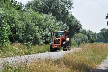 Eine Landstraße, das Straßenbegleitgrün wird von einer Landmaschine gemäht