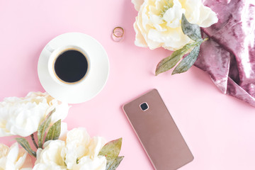 Cup of coffee and phone on the pink background with peony around