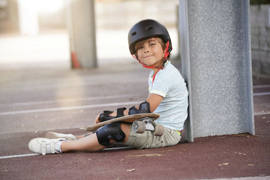 Young boy with skateboard sitting on the ground
